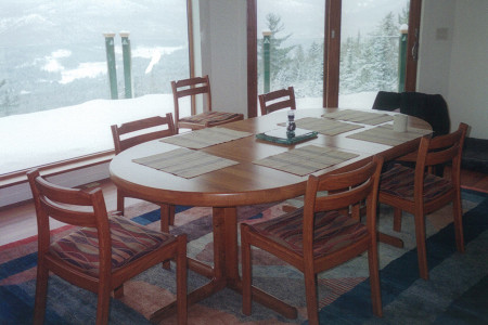 Teak dining table with 10 upholstered chairs.
