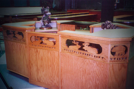 Western motif for dual station checkout: illuminated merchandise display in front, wildlife inset is backlit with bronze tinted glass, poly octagon shape funnels the crowds, clerks can efficiently work a full shift standing or sitting.