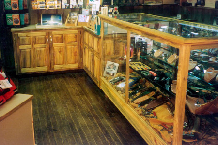 Weathered barnwood: illuminated glass jewelry counter with mirrored doors.