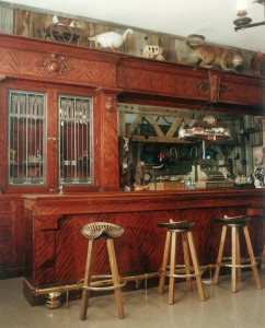 """32' Mahogany Bar  c. 19th century: shipped via clipper ship from England round the """"horn"""", to San Francisco, then onto Butte, Montana, then Death Valley and finally into Yellowstone. After decades in storage I was hired to reconstruct and rebuild, but with no photos, no drawings and no clue, yet many missing pieces, panels and embellishments, this project amounted to a massive and complex blind jigsaw puzzle. I left the dated graffiti and more than one bullet hole, but toned them down on the 2 matching 16' mahogany bar slabs."""